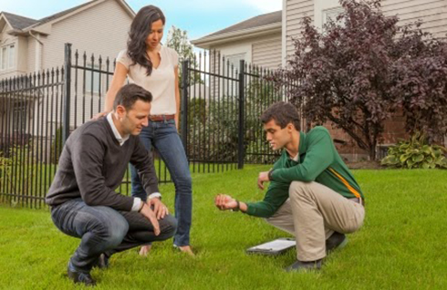 Weed Man technician on the lawn with customers